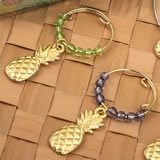 Set of four tropical gold pineapple wine charms decorated with different colored beads.